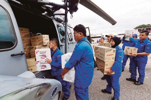 ANGGOTA Jabatan Pertahanan Awam Malaysia (JPAM) dan anggota tentera daripada 21 Rejimen Askar Melayu Diraja (21 RAMD) Angkatan Tentera Malaysia (ATM) memasukkan  barang  bantuan ke dalam lori untuk dihantar kepada mangsa banjir di Kuala Krai.