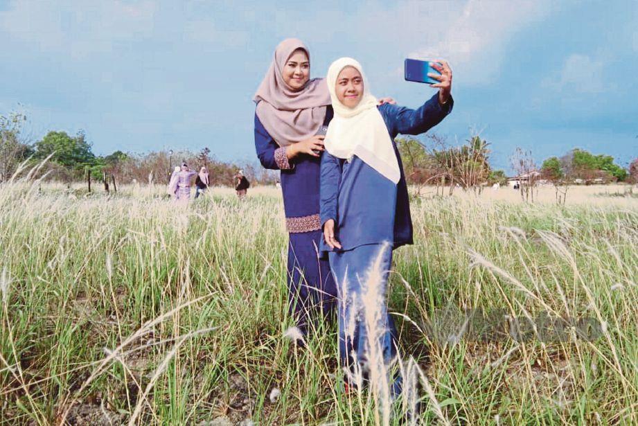 ORANG ramai tidak melepaskan peluang merakam gambar kenangan di kawasan padang yang ditumbuhi bunga lalang.