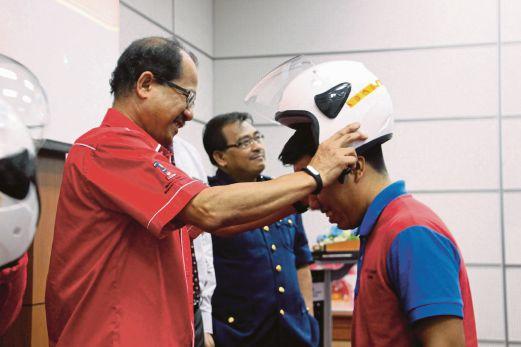Abd Ghafar (kiri) memakaikan topi keledar kepada seorang pelatih Kolej Komuniti Ledang.