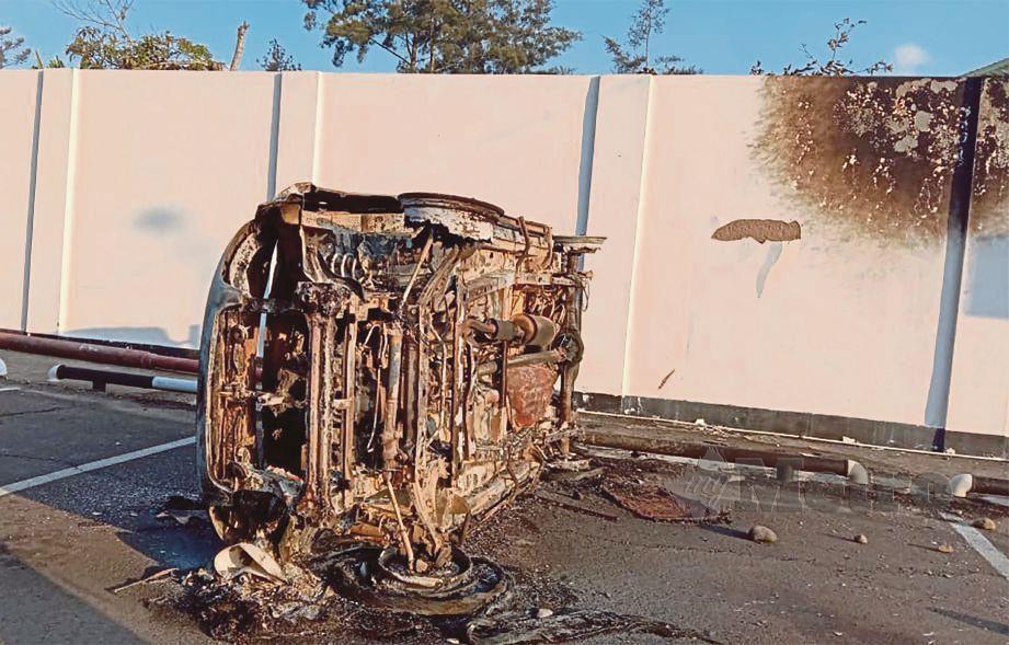 KERETA terbakar dan diterbalikkan. - AFP