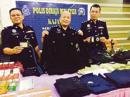 Willey (tengah) menunjukkan barangan yang dirampas daripada suspek menyamar pegawai kastam.