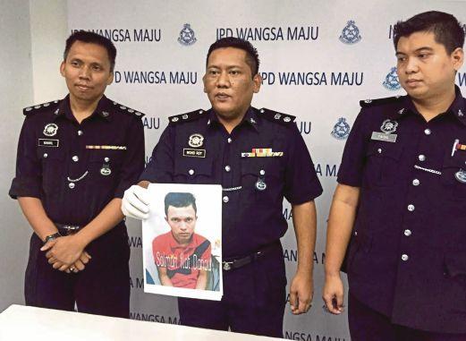 Mohd Roy (tengah) menunjukkan suspek yg diburu.