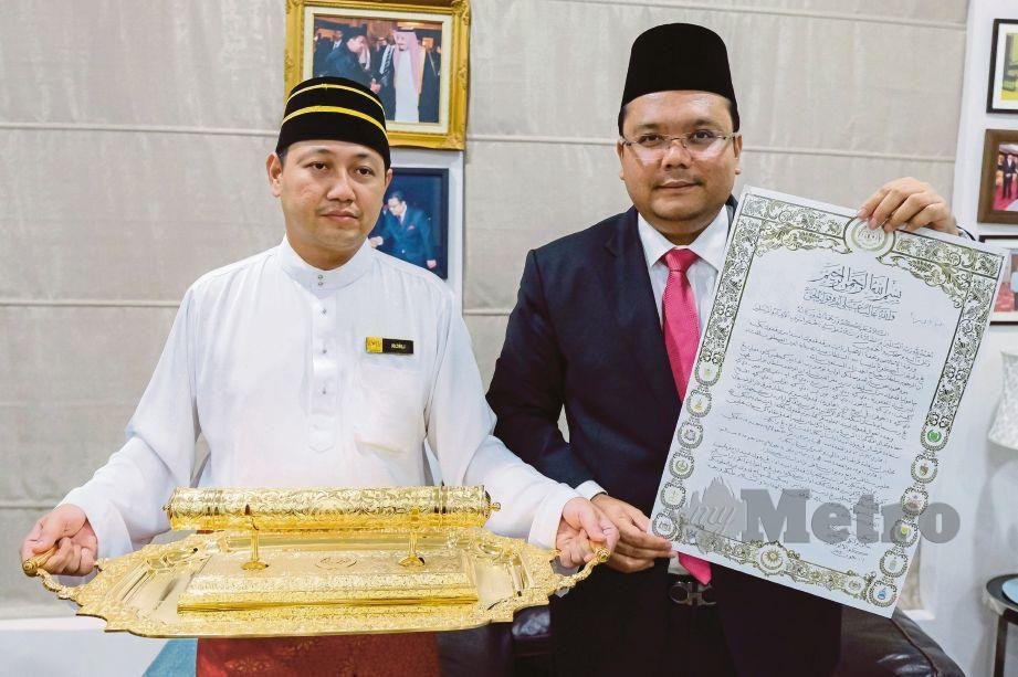 AZUAN Effendy (kanan) menunjukkan Warkah Persilaan bagi mengundang Raja-Raja Melayu dan Yang di-Pertua Negeri untuk mencemar duli ke Istiadat Pertabalan Yang di-Pertuan Agong Al-Sultan Abdullah Ri'ayatuddin Al-Mustafa Billah Shah pada 30 Julai ini.