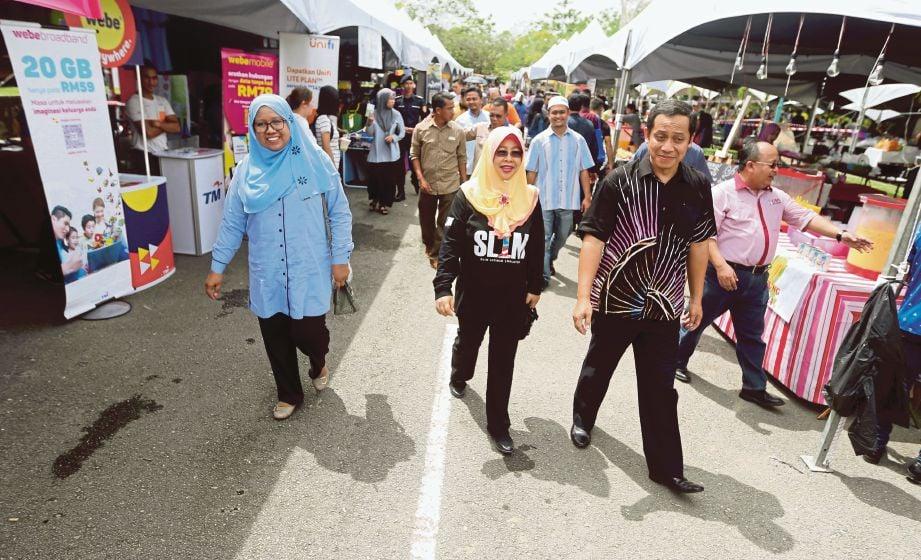 NORASHIKIN (tengah) diiringi Naib Canselor UMS, Prof Dr D Kamaruddin D Mudin melawat gerai jualan yang ditawarkan percuma kepada peniaga.