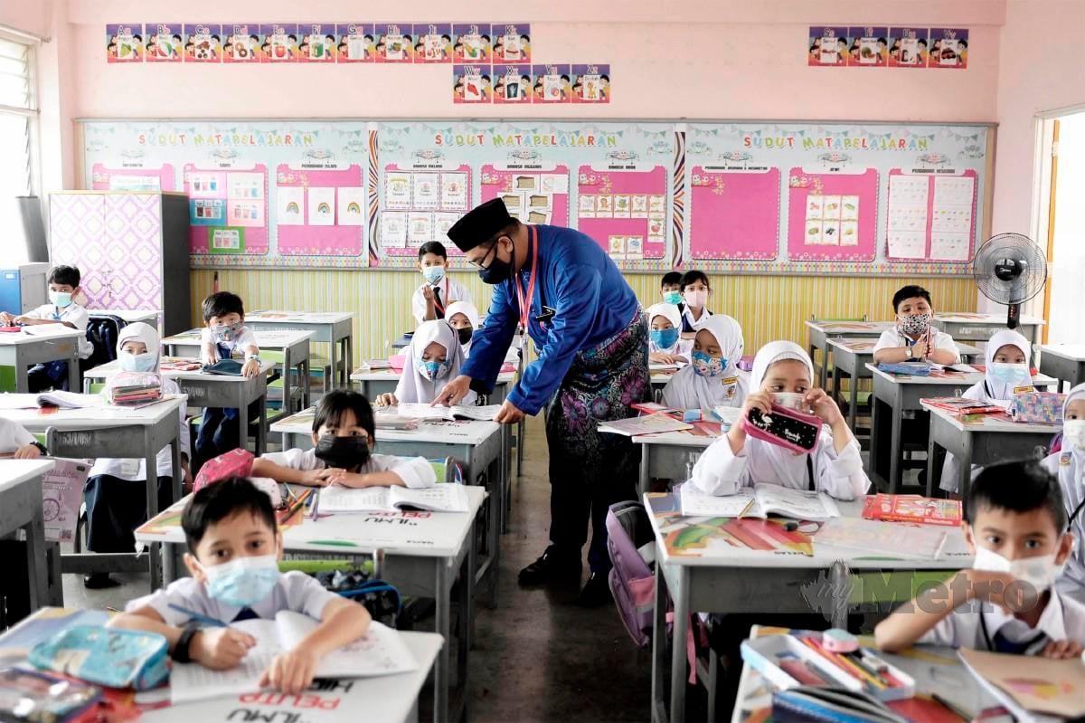 NOR Azli  mengajar anak muridnya  di Sekolah Kebangsaan Seri Permaisuri, Cheras.