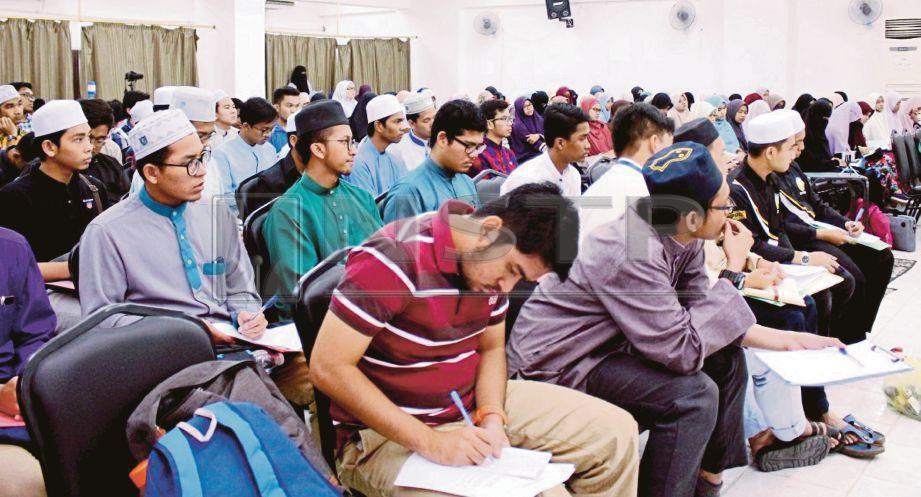 PELAJAR menyalin nota ketika sesi bengkel bahasa Arab.
