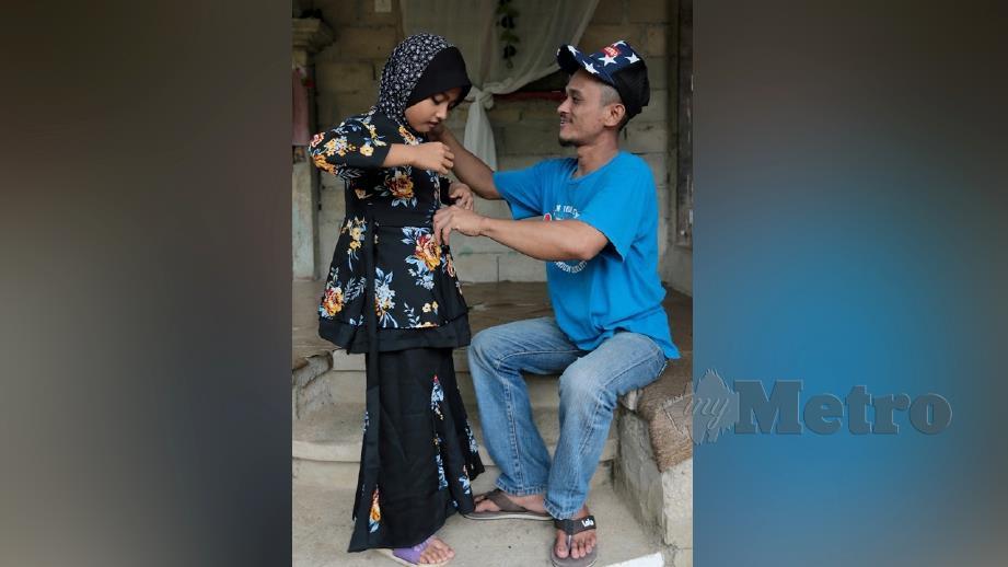 ADNAN Abdullah, 27 memakaikan baju raya kepada anaknya, Siti Hajar Qistina di Kampung Gual Jedok. FOTO Fathil Asri