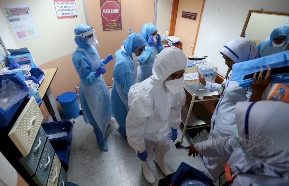 PETUGAS barisan hadapan terdiri dari doktor dan jururawat di Hospital Kuala Lumpur memakai PPE sebelum memasuki wad 28 untuk merawat pesakit. FOTO arkib NSTP