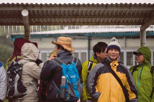 BEBERAPA pendaki menunggu bas di sebuah perhentian yang dilitupi dengan salji tebal di Tai Mo Shan, Hong Kong.