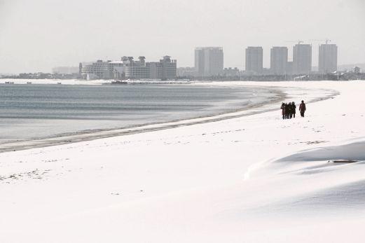 ORANG awam berjalan di atas pantai di Rongcheng, Wilayah Shandong yang dilitupi salji tebal.