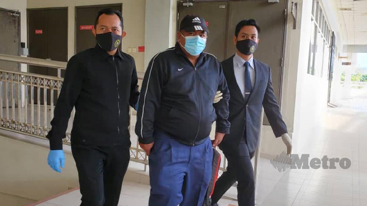 TERTUDUH (tengah) dibawa pegawai SPRM ke mahkamah. FOTO ihsan SPRM