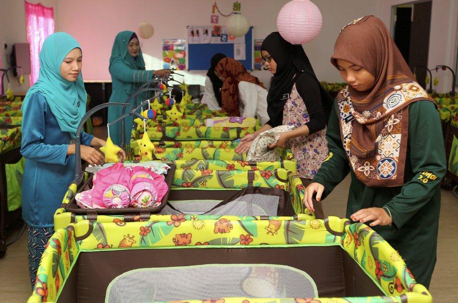 KAKITANGAN Tadika dan Taska Sinar Nur Kasih membersihkan katil kanak-kanak untuk membasmi kuman berikutan penyakit HFMD  di Anak Bukit. FOTO/SHARUL HAFIZ ZAM
