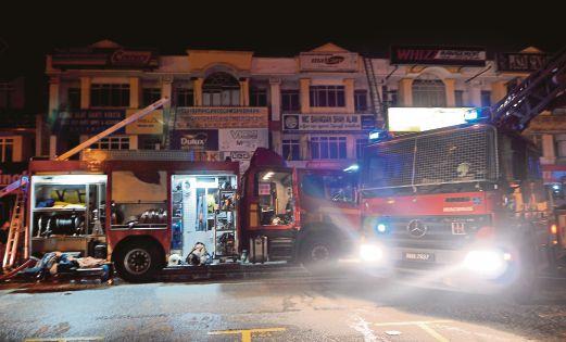 ANGGOTA bomba memadam kebakaran menggunakan kren.