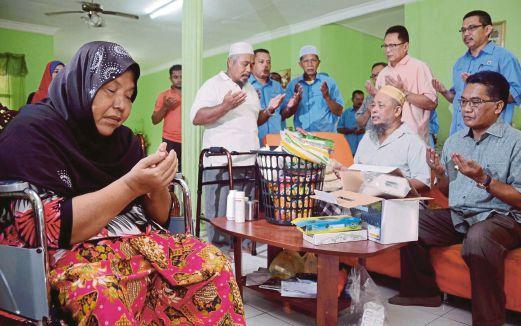 MARIAM dan Md Sidek (duduk dua dari kanan) serta Mohd Puad (berdiri dua dari kanan) mengaminkan doa dibaca.