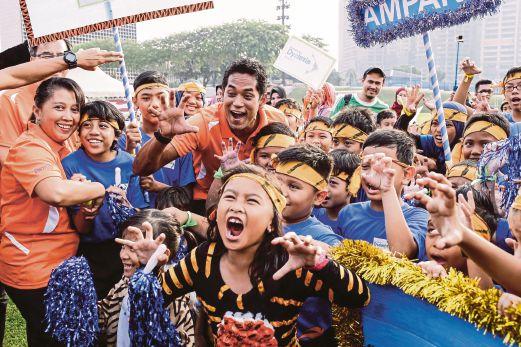 KHAIRY (tengah) bersama kanak-kanak Disleksia yang turut menyertai Sukaneka Kesedaran Disleksia di Padang Kelab Kilat TNB Bangsar.