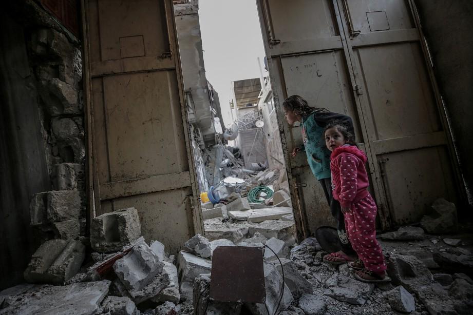 DUA beradik melihat lokasi Hamas yang dimusnahkan dalam serangan udara Israel berhampiran kediaman mereka di Gaza City. FOTO EPA