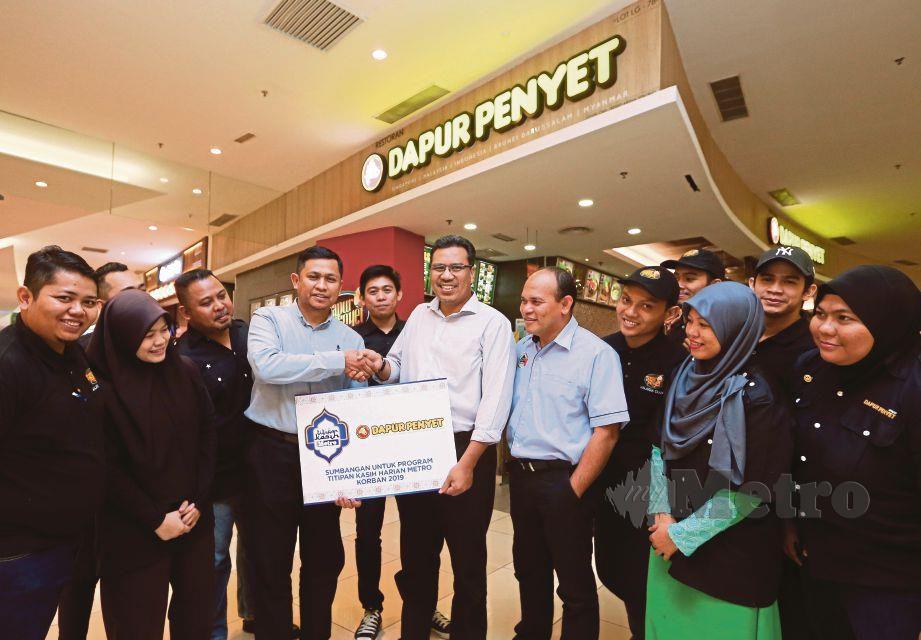 Amran (empat dari kiri) menyampaikan tajaan kepada Tuan Mohd Asri (tengah) untuk menjayakan Program Titipan Kasih Harian Metro Korban 2019 bersama Dapur Penyet.