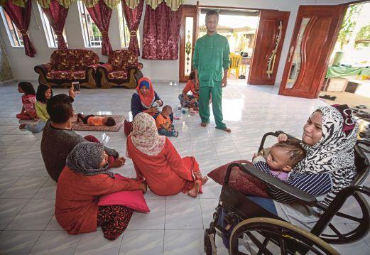 ECAH (kanan) berehat di rumah bersama ahli keluarganya.