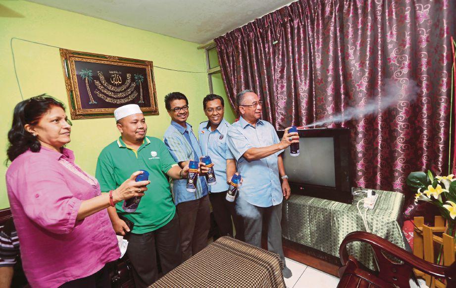 MOHD Azizi (kanan) menyembur aerosol di dalam rumah penduduk di Gugusan Melor, Kota Damansara.