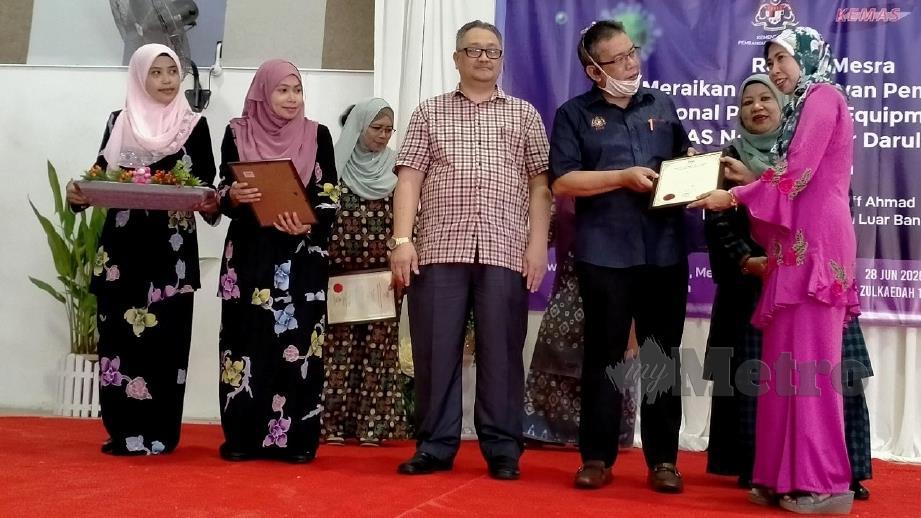 ABD Latiff (tiga kanan) menyampaikan sijil penghargaan kepada wakil sukarelawan KEMAS yang menjahit PPE. FOTO Omar Ahmad