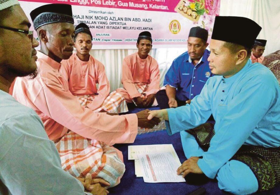 OSMAN (kanan) menikahkan  seorang peserta pada Program Pernikahan Perdana di Kampung Pasir Linggi.
