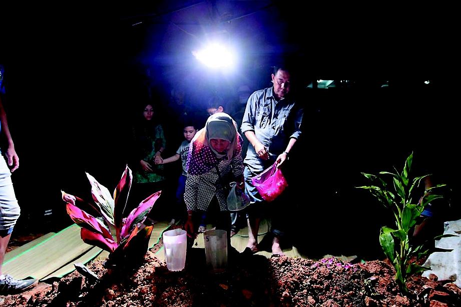 NOORSHIAH menjirus air di pusara  Allahyarham Kamarul Efindi di Tanah Perkuburan Pantai Dalam, malam tadi.