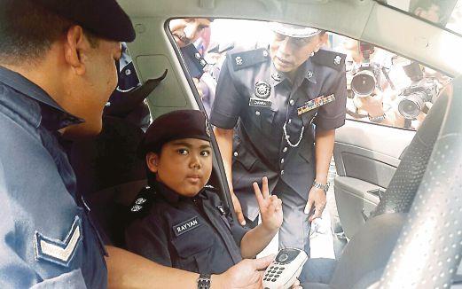 Zulkifli  (kiri) mengajar Rayyan  memberikan arahan kepada anggota polis sebelum menangkap 'penjenayah'.