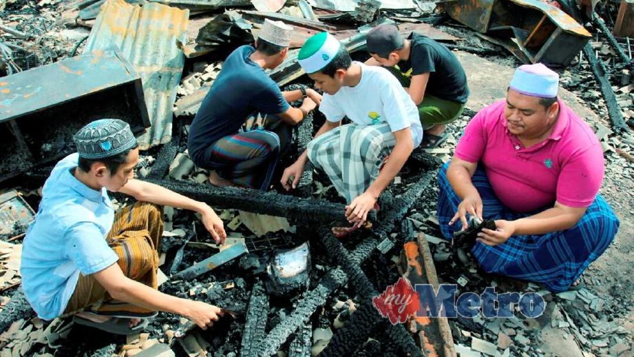 PELAJAR pondok mencari barangan yang masih boleh digunakan selepas kebakaran. FOTO Nik Abdullah Nik Omar