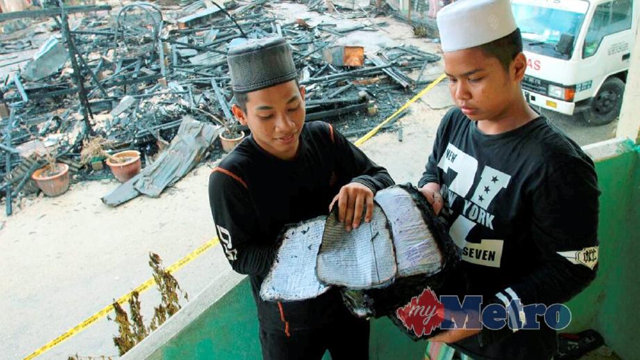 PELAJAR, Nik Mohd Nabil Nassir, 18, (kiri) dan Mohd Syahir Asri, 14, melihat kitab yang terbakar. FOTO Nik Abdullah Nik Omar