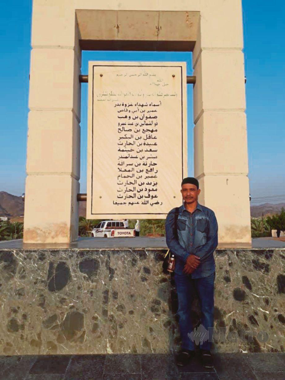 MOHD Nosdin bergambar berhampiran tugu serta makam syuhada dalam Perang Badar.