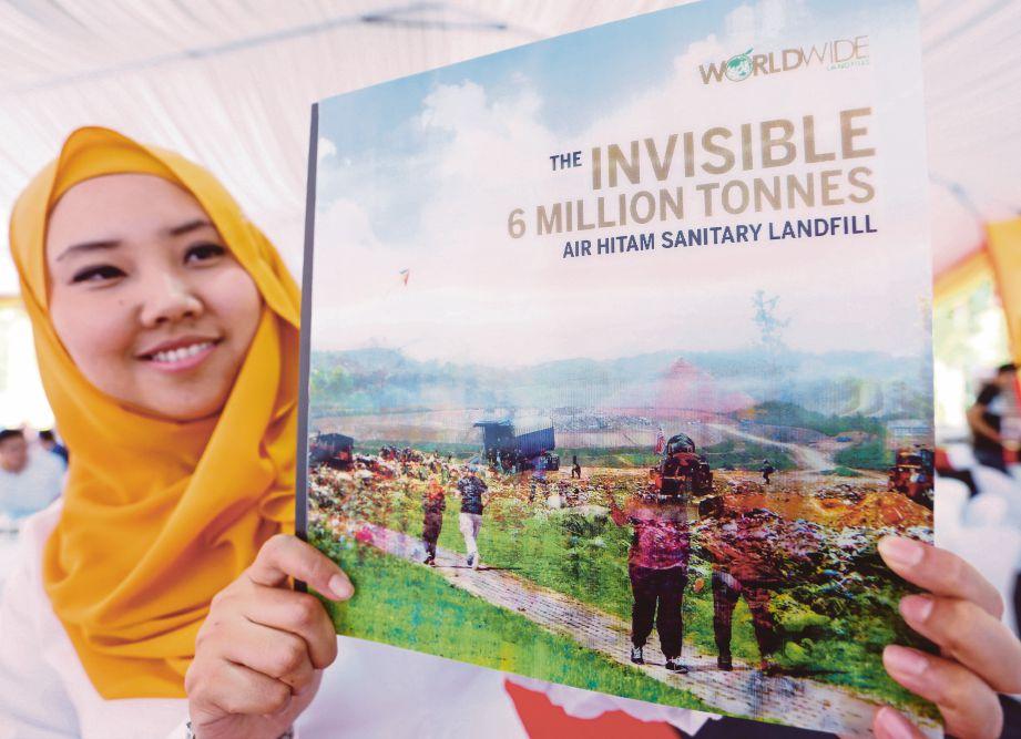KAKITANGAN Worldwide menunjukkan buku The Invisible 6 Million Tonnes Air Hitam Sanitary Landfills Park.