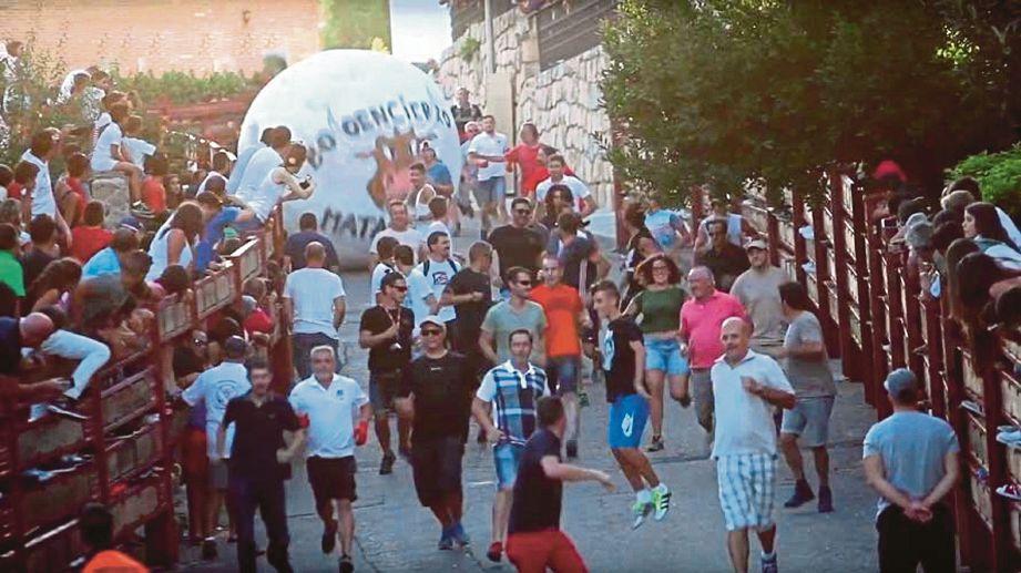 PESERTA yang menyertai pesta di Mataelpino, Sepanyol berlari bagi mengelak dilanggar bola gergasi. - Agensi