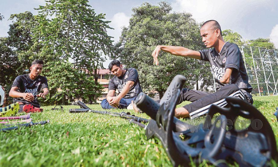 PEMAIN pasukan bola sepak orang kudung memanaskan badan sebelum memulakan latihan.