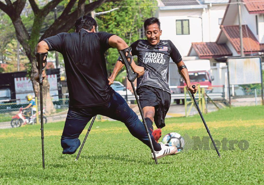 DUA pemain bola sepak orang kudung merebut bola ketika latihan.