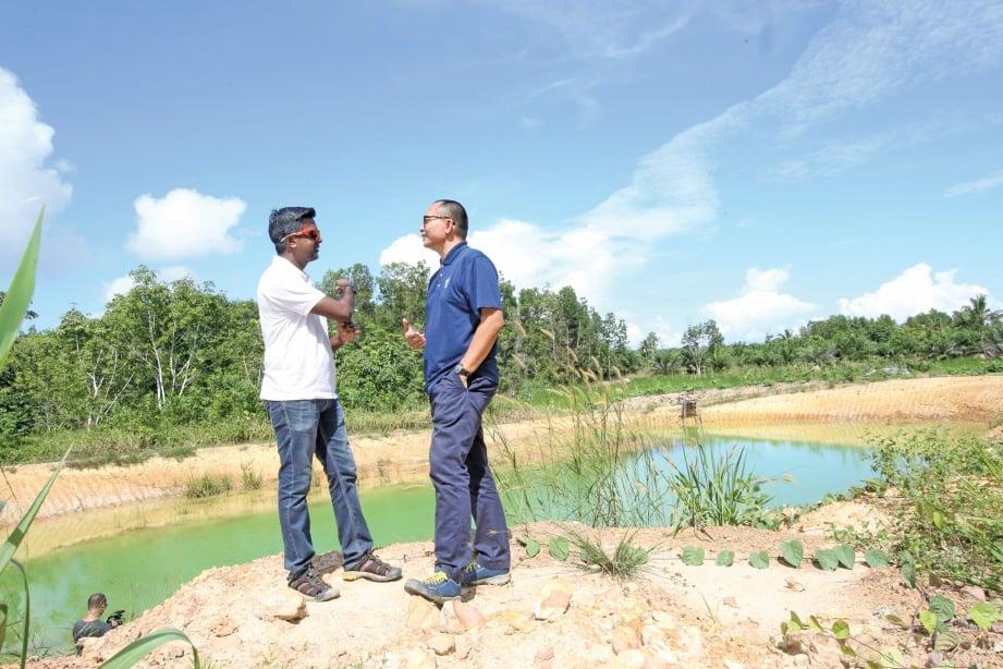 DR Anbarasu (kiri) dan Badrul meninjau kolam mengandungi bakteria E Coli,