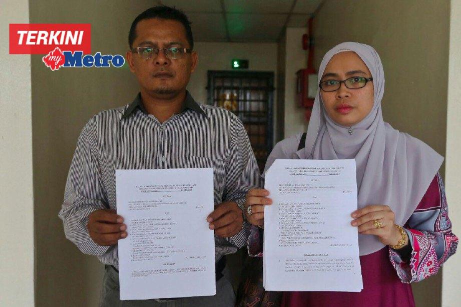 Ahmad Fauzi dan Rusaila menunjukkan surat tuntutan terhadap sembilan pihak berkaitan kejadian buli menimpa anaknya. FOTO Ghazali Kori