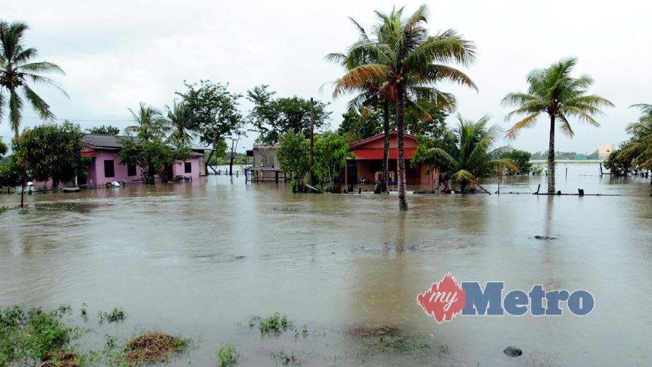 KEADAAN banjir termenung di kawasan bendang di Kampung Pulau Ular, Tumpat berdekatan Jalan Kasban selepas air Sungai Golok mula melimpahi tebing. FOTO Syamsi Suhaimi