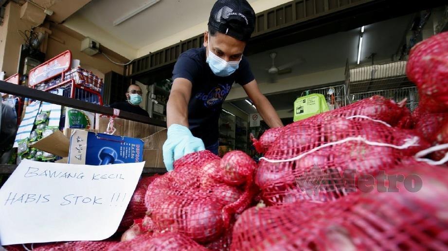 PELANGGAN memilih bawang besar di kedai runcit di Pekan Jitra Lama, semalam. FOTO Amran Hamid