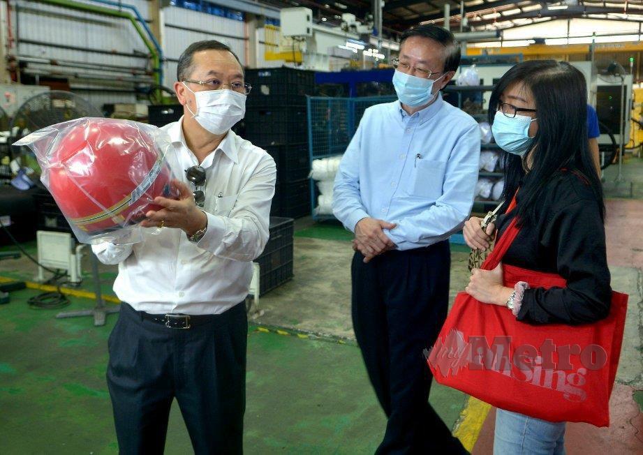 LEONG (kiri) menunjukkan antara produk yang dihasilkan ketika lawatan bersama media ke Kilang Mah Sing Plastics di  Pelabuhan Klang.
