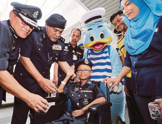 FARIS  memberi tabik hormat selepas  Mohan  (dua dari kiri) menyarungkan beret polis ketika melawatnya di PPUM.