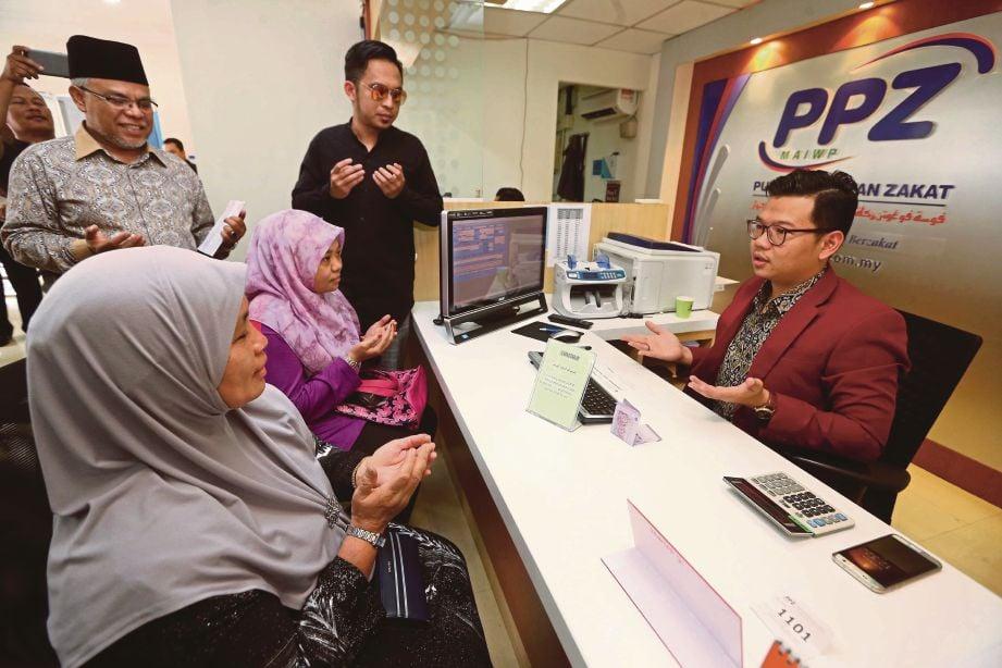 ABDUL Hakim (kiri) dan Mawi  melihat Shamisah Daud (duduk, kiri) dan Nurain Jaafar membayar zakat di Kaunter Zakat PPZ-MAIWP, Masjid Negara.