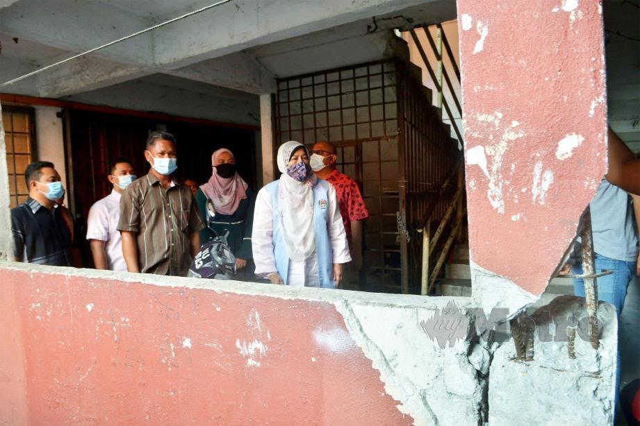 ZURAIDA (kanan) melihat keadaan struktur bangunan yang mengalami keretakan ketika mengadakan lawatan di flat Taman Sri Berembang.