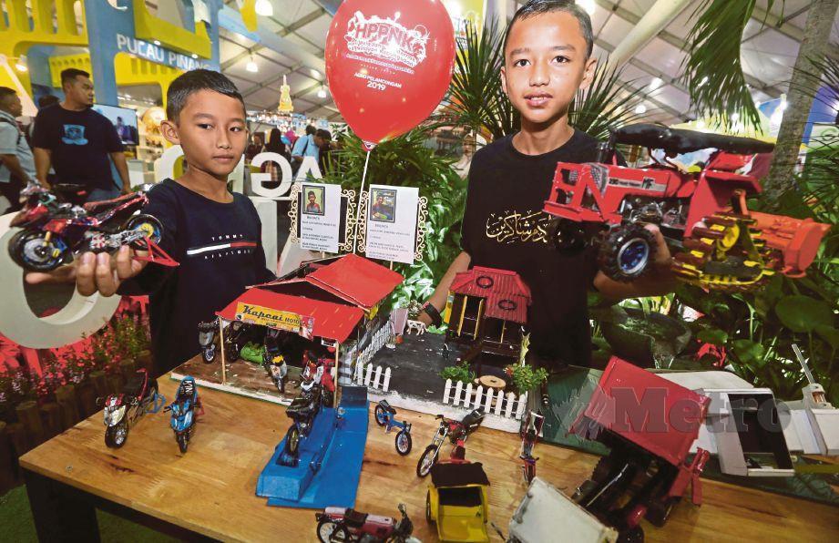 MUHD Adam Shakirin Mohd Fuad (kanan) dan adiknya, Muhd Azim Hafifi menunjukkan  replika permainan yang dibuat menggunakan barangan terbuang.