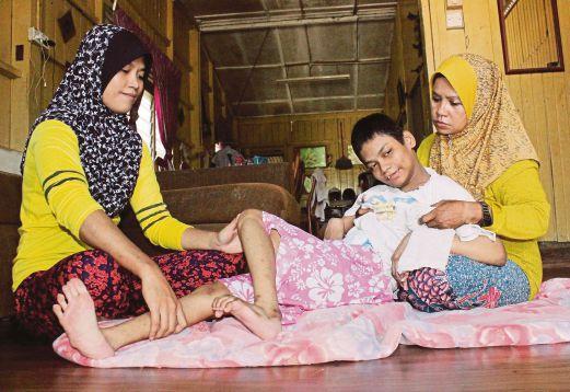 CHE Minah (kanan) menguruskan Nurhanani.