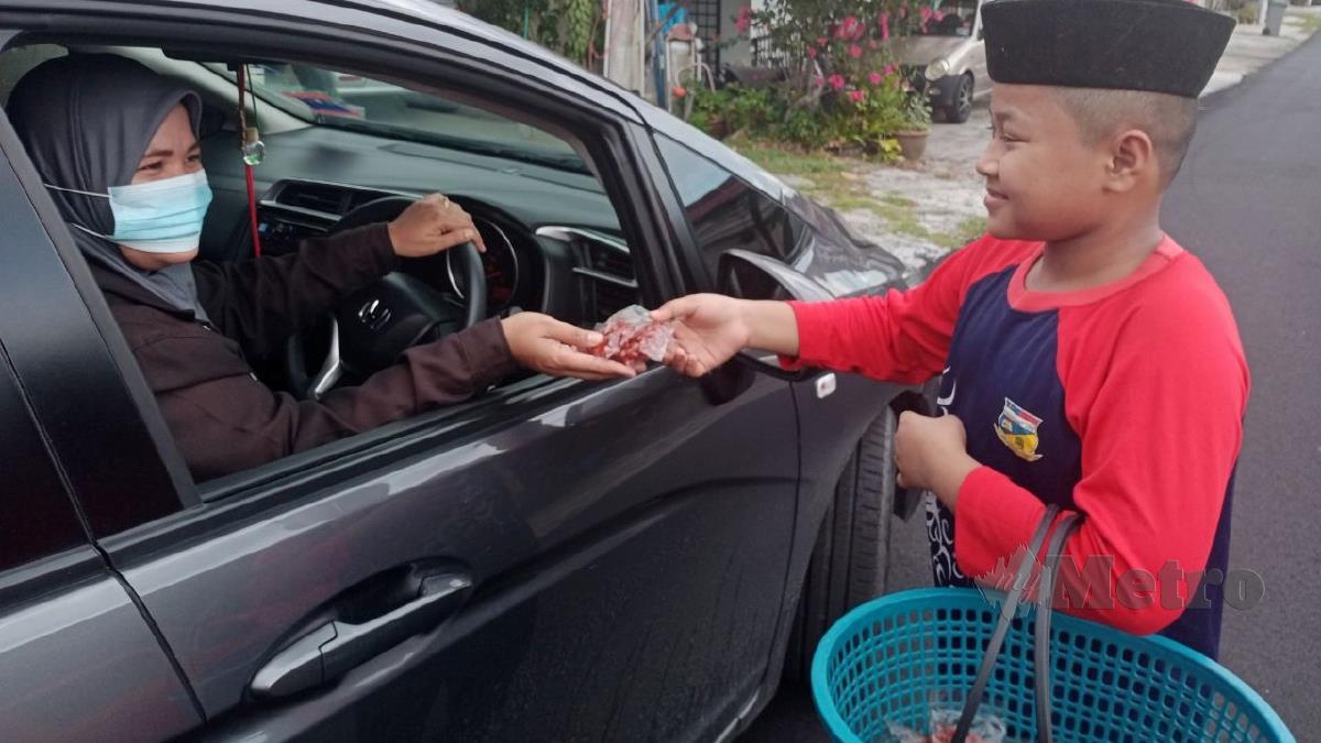 MUHAMMAD Alif menjual kacang goreng sambal kepada pelanggannya. FOTO Mohd Khidir Zakaria