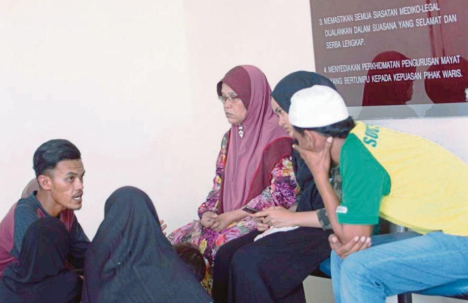 AHLI keluarga mangsa menunggu jenazah lelaki yang mati dipukul dalam kejadian Ahad lalu.