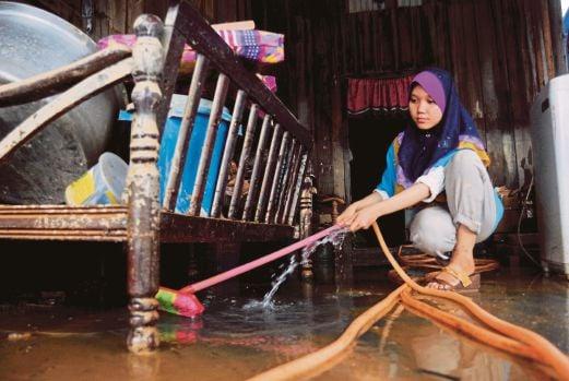 MANGSA banjir Siti Zulaiha Che Mat membersih lumpur di dalam rumahnya.