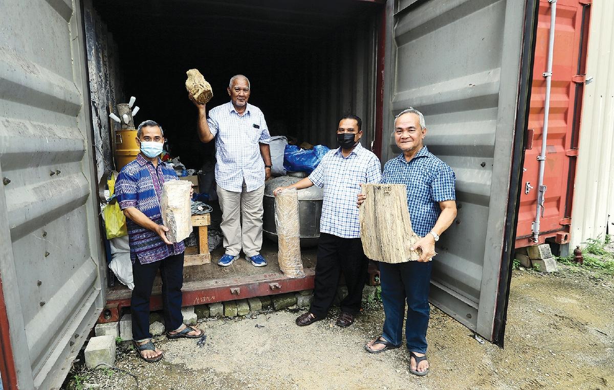 SARIPPUDIN (dua dari kiri) menunjukkan kayu gaharu yang belum diproses.