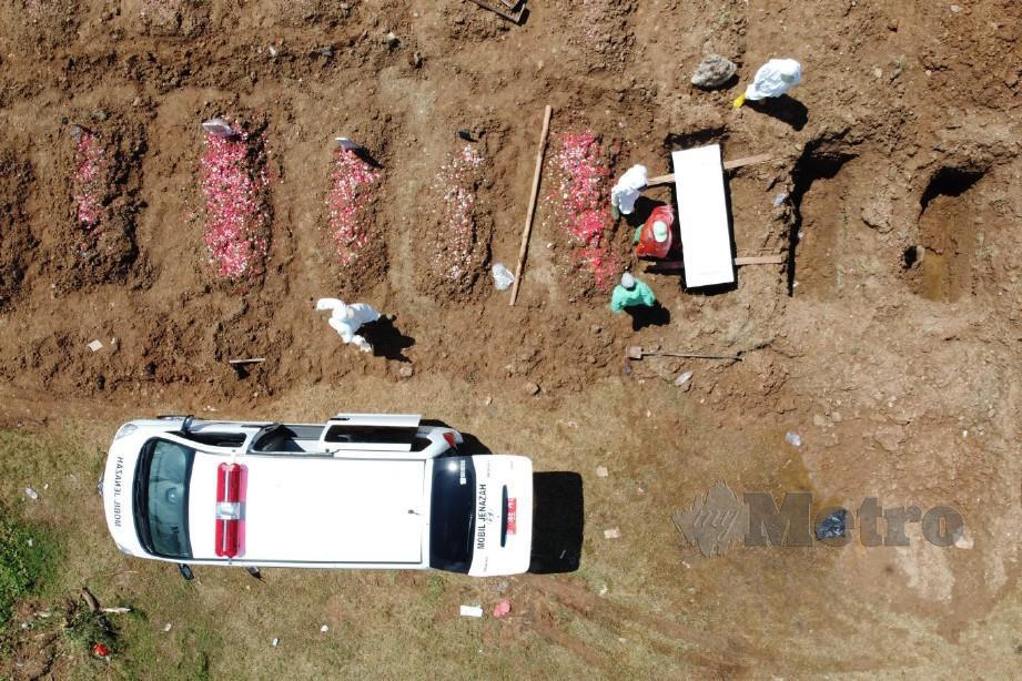 PETUGAS Badan Perhutanan dan Taman Jakarta mengebumikan jenazah pesakit yang meninggal dunia akibat koronavirus di Tanah Perkuburan Awam Tegal Alur, Jakarta Barat. FOTO Jakarta Post.
