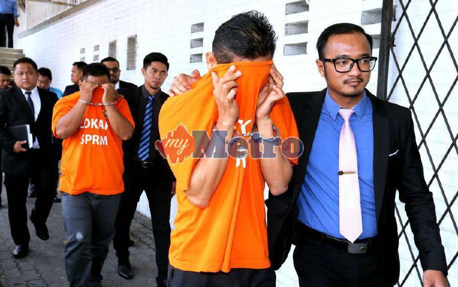 Pegawai SPRM membawa individu yang ditahan untuk siasatan kes rasuah JKNS ke Mahkamah Majistret Kota Kinabalu, hari ini. FOTO Khairull Azry Bidin